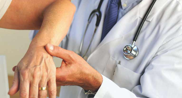 A doctor holding a womans arm in neuropathy pain